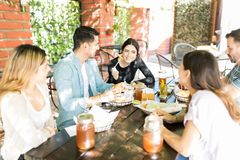 Friends Enjoying Social Gathering Time At Burger Shop. Beautiful young women having food while talking with pals at fast food restaurant royalty free stock images