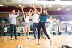 Friends Enjoying Victory At Bowling Club. Happy multi-ethnic friends enjoying victory while standing at bowling club royalty free stock photo
