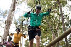Friends enjoying zip line adventure in park. On a sunny day Stock Photos