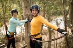 Friends enjoying zip line adventure in park. Happy friends enjoying zip line adventure in park Stock Photos