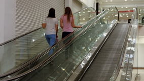 Friends on the escalator in mall. In high quality format stock video footage