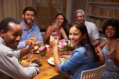 Friends at an evening dinner party, looking at camera stock photography