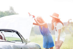 Friends examining broken down car on sunny day Royalty Free Stock Photography