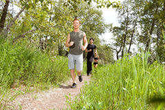 Friends exercising in forest track Royalty Free Stock Photos