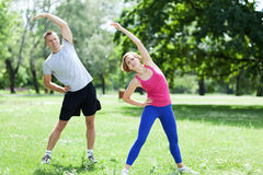 Friends Exercising In Park Stock Images