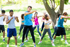 Friends exercising in park. Group of multiethnic friends exercising in park royalty free stock image