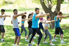 Friends exercising in park. Group of multiethnic friends exercising in park stock photos