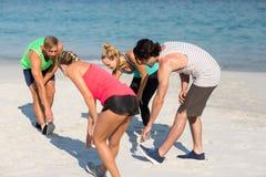 Friends exercising on shore at beach Stock Photos