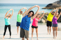 Friends exercising while standing on shore Stock Photos