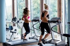 Friends  exercising on a treadmill at the bright modern gym Royalty Free Stock Images