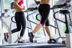 Friends  exercising on a treadmill at the bright modern gym Royalty Free Stock Photo