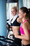Friends  exercising on a treadmill at the bright modern gym Royalty Free Stock Photography