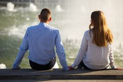 Friends fall in love. Young shy people sitting near fountain hol stock images