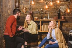Friends, family spend pleasant evening, interior background. Family enjoy conversation in gamekeepers house. Girls and. Men on relaxed faces hold metallic mugs royalty free stock photography