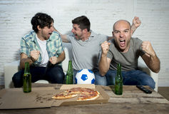 Friends fanatic football fans watching game on tv celebrating goal screaming crazy happy Stock Photography