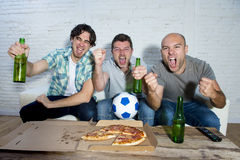 Friends fanatic football fans watching game on tv celebrating goal screaming crazy happy. Group of friends fanatic football fans watching soccer game on Stock Images