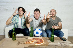 Friends fanatic football fans watching tv match with beer bottles and pizza suffering stress. Group of friends fanatic football fans watching soccer game on Royalty Free Stock Image