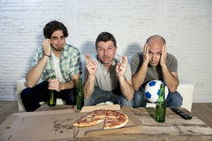 Friends fanatic football fans watching tv match with beer bottles and pizza suffering stress Royalty Free Stock Photography