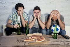 Friends fanatic football fans watching tv match with beer bottles and pizza suffering stress Royalty Free Stock Image