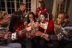 Friends In Festive Jumpers Celebrate At Christmas Party Stock Photos