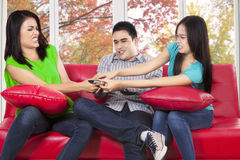 Friends fighting for remote tv stock photo