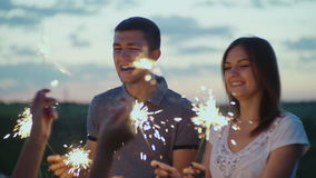 Friends with fireworks in their hands having fun at a party in the evening. Slow motion video stock video