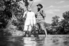 Friends fishing. Elegant bearded man and brutal hipster fishing. Perfect weekend. Family day. Summer vacation. Fishing