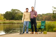 Friends with fishing rod and net at lake or river. Leisure and people concept - happy male friends with fishing rod and scoop net hugging at lake or river royalty free stock photo