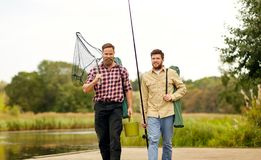 Friends with fishing rods and net at lake or river. Leisure and people concept - happy friends with fishing rods and scoop net walking along wooden pier at lake royalty free stock photos