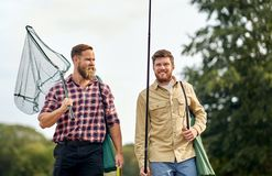 Friends with fishing rods and net outdoors. Leisure and people concept - happy friends with fishing rods and scoop net outdoors stock image