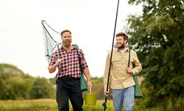 Friends with fishing rods and net walking outdoors. Leisure and people concept - happy friends with fishing rods and scoop net walking outdoors royalty free stock image