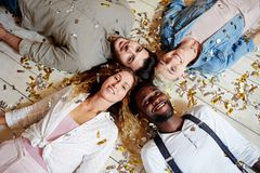 Friends on the floor. Four intercultural friends lying head to head on the floor covered with confetti Royalty Free Stock Photos