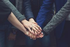Friends folded their hands together. A company of friends folded their hands together. Close up Royalty Free Stock Photography