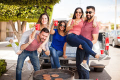 Friends fooling around and having fun. Group of good looking Hispanic friends drinking beer and having some fun together at a barbecue royalty free stock images