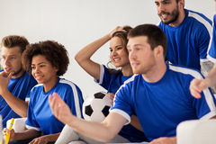 Friends or football fans watching soccer at home Royalty Free Stock Image