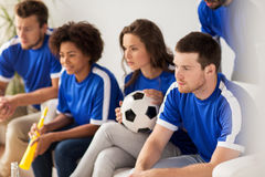 Friends or football fans watching soccer at home. Friendship, leisure, sport and entertainment concept - happy friends or football fans watching soccer at home Stock Image