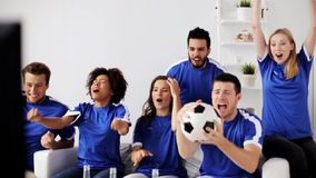 Friends or football fans watching soccer at home stock video footage