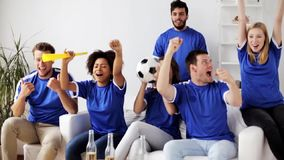 Friends or football fans watching soccer at home stock footage