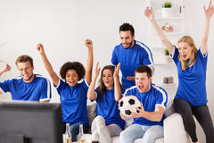 Friends or football fans watching soccer at home Stock Photos