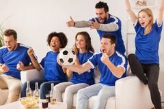 Friends or football fans watching soccer at home. Friendship, sport, people and entertainment concept - happy friends or football fans watching soccer and Royalty Free Stock Photography