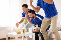 Friends or football fans watching soccer at home. Friendship, sport, people and entertainment concept - happy male friends or football fans watching soccer at Royalty Free Stock Photos