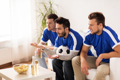 Friends or football fans watching soccer at home. Friendship, sport, people and entertainment concept - happy male friends or football fans watching soccer on tv Stock Photo