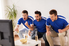 Friends or football fans watching soccer at home. Friendship, sport, people and entertainment concept - happy male friends or football fans watching soccer on tv Stock Photography