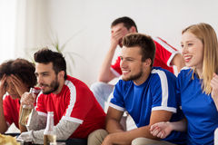 Friends or football fans watching soccer at home Stock Photo