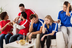 Friends or football fans watching soccer at home Royalty Free Stock Photos