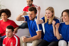 Friends or football fans watching soccer at home. People, leisure, rivalry and sport concept - happy friends or football fans watching soccer game or match and Stock Images
