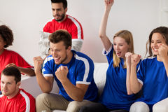 Friends or football fans watching soccer at home. People, leisure, rivalry and sport concept - happy friends or football fans watching soccer game or match and Royalty Free Stock Photo