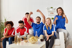 Friends or football fans watching soccer at home Royalty Free Stock Images