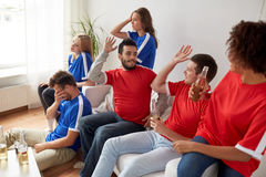 Friends or football fans watching soccer at home Royalty Free Stock Photography
