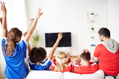 Friends or football fans watching tv at home Royalty Free Stock Photos